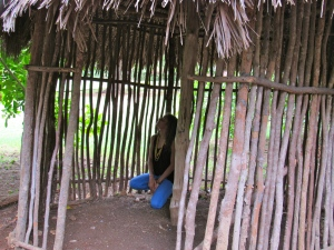 Poet Yashika Graham inside a replica Taino dwelling, made of sticks with a thatched roof - light and yet with a certain delicacy and strength.