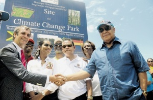 German ambassador to Jamaica Josef Beck (left) and Jamaica's Minister of Water, Land, Environment and Climate Change Robert Pickersgill shake hands at the unveiling of the sign declaring the open lot across from the Portmore Mall the site of the Climate Change Park. They are joined by (from second left) Member of Parliament for East Central St Catherine and junior foreign affairs minister Arnaldo Brown; Minister of Youth and Culture Lisa Hanna; Member of Parliament for South East St Catherine and junior local government minister Colin Fagan; Minister of Local Government and Community Development Noel Arscott; and councillor for the Greater Portmore East Division Yvonne McCormack. The Climate Change Park was the National Labour Day project for 2014. (Photo: Jamaica Observer)