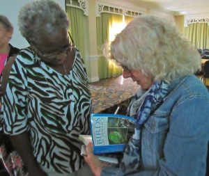 "Dr. Anne Sutton (right) autographs a copy of her book ""A Photographic Guide to the Birds of Jamaica"" for Linnette Vassell on Jamaica Day at the BirdsCaribbean conference."