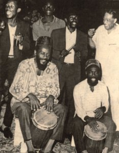 This wonderful photograph shows Count Ossie playing the tall burru drums, while the legendary American jazz musician/composer Duke Ellington (far right) looks on. The Rastafarian movement adopted the burru drum into their nyabinghi rhythms and practices.