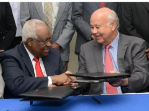 These two men now control most of the existing media landscape: RJR Group chairman, Lester Spaulding (left) and The Gleaner's Chairman, Oliver Clarke, exchange documents sealing the deal of the merger. (Photo: Gleaner)