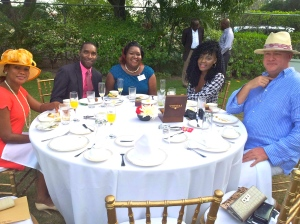 Chevening Scholar Chadine Allen (in teal blue) and Fulbright Scholar Dr. Damion McIntosh (in pink shirt) with friends and family at the Chevening tea party. (My photo)