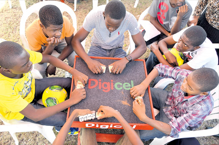 Boys enjoy a game of dominoes during a Digicel-sponsored initiative for at-risk young men in 2013. (Photo: Jamaica Observer)