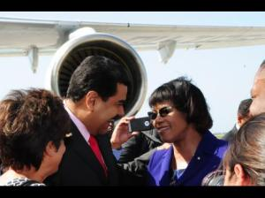 An attempt at a selfie? Prime Minister Portia Simpson Miller (left) greets Venezuelan President Nocolas Maduro at the Donald Sangster International Airport in Montego Bay on Saturday. (Photo: Paul Clarke/Gleaner)