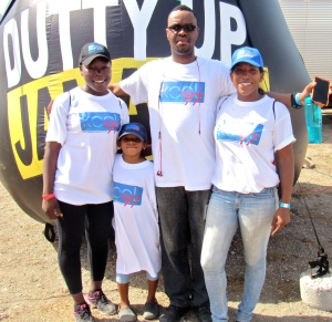 """The KOOL FM family pose for their picture in front of an inflatable """"Nuh Dutty Up Jamaica"""" bag. Note the latest style in T shirts (full length for children!)"""