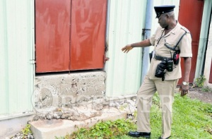 A police officer points to bloodstains on the step of the Greater Work Revival Mission Church in Mud Town, St. Andrew, where Pastor David Roper was shot dead on Wednesday night. (Photo: Jamaica Observer)