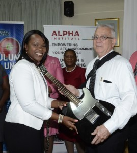 Is Education Minister Ronald Thwaites going to burst into a blistering guitar riff, Jimi Hendrix-style? I think not, but here he is receiving musical gifts along with Ms. Kasan Troupe, Principal of Denbigh High School. Denbigh as well as Papine High School and the Alpha Institute benefited from the gifts of musical instruments. (Photo: Jamaica Information Service)