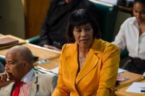 The Prime Minister, in party colors, stands up in Parliament to congratulate our successful athletes. (Photo: Jamaica Information Service)
