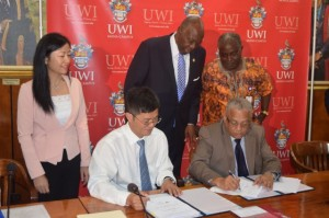 Minister of Health, Hon. Dr. Fenton Ferguson (centre, standing), observes while Principal of the University of the West Indies, Professor Archibald McDonald (right), and Deputy General Manager at China Engineering Company (CHEC), Qiwu Yang (left), sign a Memorandum of Understanding (MoU) for a $60 billion expansion programme at the University of the West Indies (UWI), on August 26, at the UWI Campus. Also pictured is Deputy Principal of the University, Professor Ishenkunba Kahwa (right, standing). Photo: Jamaica Information Service