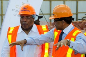 Hard hat photo-op: Industry, Investment and Commerce Minister, Hon. Anthony Hylton (left), listens as Chief Executive Officer of Kingston Wharves Limited, Grantley Stephenson, provides an update on the progress of work on the construction of a 160,000-square foot Total Logistics Facility at Newport West, Kingston, during a tour on October 7. (Photo: Jamaica Information Service)