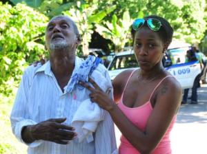 Errol Mangaroo, the father of Byron Mangaroo being comforted by a family friend. Byron was one of six family members murdered in Hanover on Thursday night. (Photo: Adrian Frater/Gleaner)