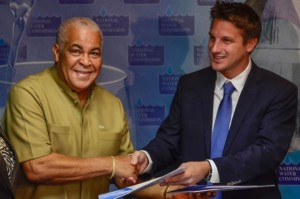 Minister of Water, Land, Environment and Climate Change, Hon. Robert Pickersgill (left), and Country Manager, Vinci Construction Grands Projets, Timothee Delebarre, symbolically exchange signed copies of the contract for the replacement/upgrading of the Boscobel and Elleston Flats Wastewater Treatment Plants. (Photo: Jamaica Information Service)