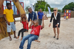 Jamaica Public Service Company (JPS) CEO Kelly Tomblin and Region Central Director Roger Kennedy give children a push on the swing in their new playground. (Photo: JPS Foundation)