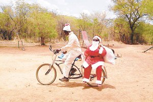 "African Santa… An article in Kenya's ""Daily Nation"" (I follow many overseas newspapers) suggests you cannot go to ""the village"" empty-handed. Here comes Santa! (Daily Nation File Photo)"