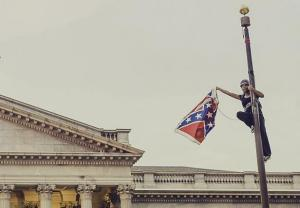 Bree Newsome takes down the Confederate Flag from a pole at the Statehouse in Columbia, South Carolina, June 27, 2015. REUTERS/Adam Anderson Photo