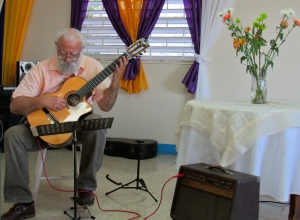 Guitarist, flowers and bright curtains. (My photo)