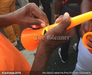 A PNP supporter scratches out the color of the opposing Tribe on her vuvuzela. (Photo: Gleaner/Twitter)