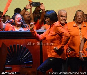 Prime Minister Portia Simpson Miller proves her fitness for office by running onto the stage.