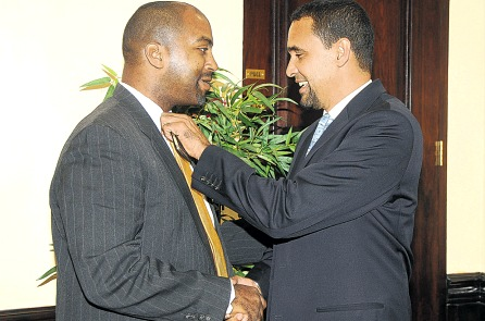 Happier times: Jamaica Labour Party deputy general secretary Ian Murray adjusts the tie of People's National Party deputy general secretary Julian Robinson before shaking hands during the signing ceremony for the national debates at The Courtleigh Hotel in Kingston on December 2, 2011. (Photo: Michael Gordon/Jamaica Observer)
