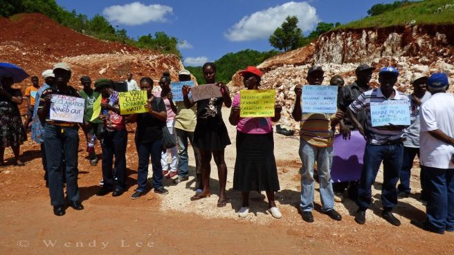 """Residents of Cockpit Country stand in protest on the roads hacked out by the bauxite company. """"We want clean drinking water"""" says one placard."""" (Photo: Wendy Lee)"""