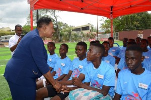 Minister of Culture, Gender, Entertainment and Sport, Hon. Olivia Grange (left), speaks to young footballers at the launch of the Digicel Kickstart Clinic 2016, held today (March 29), at the Whole Life Sports Centre, Devon Road, in Kingston. (Photo: Jamaica Information Service)