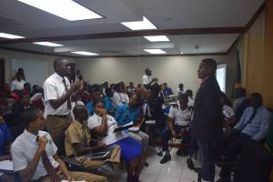 State Minister in the Ministry of Education, Youth and Information Floyd Green (standing) listens to high school students at a recent meeting. (Photo: Youth Information Centres)