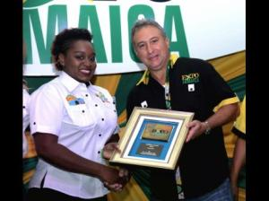 Dadre-Ann Graham, sales representative at GraceKennedy, receives the exhibitor award for the Best Environmentally Friendly Exhibit/Product from Metry Seaga, president of the Jamaica Manufacturers' Association, during Expo Jamaica 2016. (Photo: Norman Grindley/Gleaner)