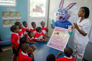 "Fun with Dr. Rabbit...Dental hygienist Tamisha Spooner demonstrates proper oral care to Union Gardens Infant School student with help from Colgate's mascot, Dr. Rabbit. The occasion was the launch of Colgate's Mobile Dental Unit on April 7. The Mobile Dental Unit is a critical component of Colgate's ""Bright Smiles, Bright Futures"" school programme which provides education and oral care for approximately 150,000 children aged 6 to years annually island-wide."