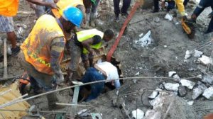 Men search under the collapsed building at the Blue Diamond Royalton Hotel yesterday. (Photo: Jamaica Observer)