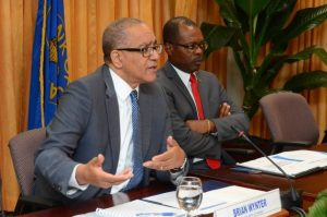 Bank of Jamaica (BoJ) Governor, Brian Wynter (left), responds to a question during the quarterly press briefing at the BoJ's headquarters, on May 26. Also pictured is the bank's Deputy Governor, Livingstone Morrison. (Photo: JIS)