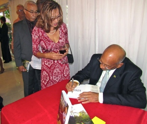 Like every good author, Mr. Orane thoroughly enjoyed signing copies of his books at the May 12 launch. (My photo)