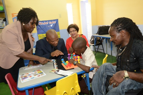 Director of the Early Stimulation Programme in the Ministry of Labour and Social Security, Mrs. Antonica Gunter-Gayle (left) interacts with a student of the Early Stimulation Centre of Excellence - Mickhail Betancourt Building. Joining her are, from left: Donovan Betancourt, father of Mickhail Betancourt, in whose honour the building is named, Jean Lowrie-Chin, Chair, Digicel Foundation, and Paralympic gold medalist, Alfonso Cunningham.