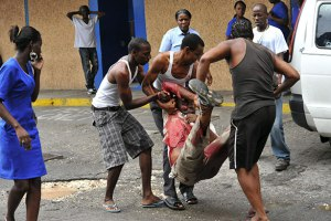 Residents carry a wounded man into Kingston Public Hospital during the incursion by security forces in Tivoli Gardens. (Photo: Guardian UK)