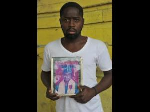 Jeff Grant, holds a youthful photograph of his nephew, Odane Bennett, who was shot and killed by the police in a bus on Olympic Way in Waterhouse, St Andrew. (Photo: Norman Grindley/Gleaner)
