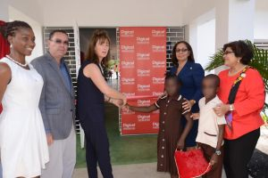 Mrs. Catherine O'Brien (3rd left), wife of Digicel's Founder and Chairman and Digicel Foundation's Patron, Hon. Denis O'Brien, OJ, is joined by students of the Early Stimulation Centre of Excellence – Mickhail Betancourt Building, as she cuts the ribbon for the official opening of the facility on Thursday, April 7 in Orange Bay, Portland. The building was named in honour of a former Digicel staff member who passed away in 2015. Joining her, from left, are Ms Imani Betancourt, sister of the deceased, Hon. Daryl Vaz, Minister without Portfolio in the Ministry of Economic Growth and Job Creation, Hon. Shahine Robinson, Minister of Labour and Social Security and Jean Lowrie-Chin, Chair, Digicel Foundation. Early Stimulation Centre of Excellence, a $30 million state-of-the-art Special Needs facility, is the seventh of 10 Centres of Excellence to be built by the Digicel Foundation by July 2016.