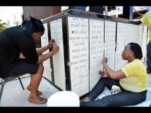 Kamesha Stevenson (left) and Sandra Kelly from Hylton's Marble Works adding more than 2,000 names of children who died tragically to the monument at Secret Gardens on Church Street in downtown Kingston. (Photo: Norman Grindley/Gleaner)