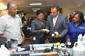 Minister of Health, Dr. the Hon. Christopher Tufton (third left), along with (from left) Chairman of the Board of Hardware and Lumber Ltd., Mr. Erwin Burton; Chief Executive Officer, Ms. Donna Duran; and General Manager of AgroGrace, Mrs. Olive Downer-Walsh, at a briefing at the company's Spanish Town Road offices on Tuesday, June 21. They are observing products being carried by the company which are used in vector control management. (Photo: JIS)