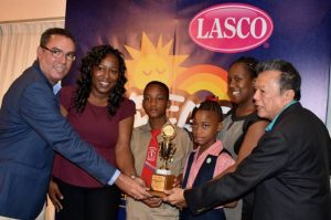Minister without Portfolio in the Ministry of Economic Growth and Job Creation, Hon. Daryl Vaz (left); and Chairman of LASCO, Hon. Lascelles Chin (right), present a trophy to teachers and students of the Howard Cooke Primary School for winning the LASCO Re-Leaf Environmental Awareness Programme (REAP) competition. From second left are: teacher, Yakiesha Smith; students, Ricardo Hamilton and Mikalia Brown; and teacher, Olivene Walker. The award ceremony was held on June 2. (Photo: JIS)