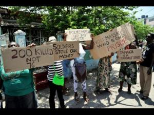 Residents of Tivoli Gardens in west Kingston protest with placards during a tour of the area, in April 24, 2015, by the commissioners and lawyers involved in the commission of enquiry. (Photo: Norman Grindley/Gleaner)