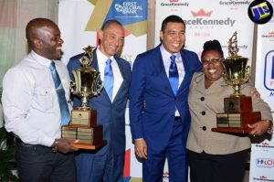 Prime Minister Andrew Holness (2nd right), along with Group Chief Executive Officer of GraceKennedy, Senator Don Wehby (2nd left), congratulate winners of the GraceKennedy/Heather Little-White Household Worker of the Year Award, Michael Lawson (left) and Millicent Clunis. The Prime Minister gave the keynote address. (Photo: JIS)