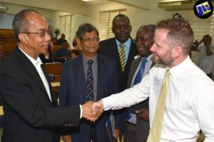 Minister without Portfolio in the Ministry of Economic Growth and Job Creation, Hon. Dr. Horace Chang (left), is greeted by Research Fellow, Institute for Advanced Sustainability Studies, Germany and Project Director at the Solar Radiation Management Governance Initiative (SRMGI), Mr. Andy Parker (right), at a workshop at the University of the West Indies (UWI), Mona, on July 7. The workshop was held to facilitate discussion on a solar radiation management (SRM) theory to reduce global warming. Also pictured are (from left) President of the Caribbean Academy of Sciences, Jamaica, Professor Tara Dasgupta; Senior Advisor on Energy in the Ministry of Science, Energy and Technology, Mr. Dwight Lewis; and Dean in the UWI Faculty of Science and Technology, Professor Ishenkumba Kahwa. The workshop was hosted by the UWI, in collaboration with SRMGI; the Caribbean Academy of Sciences, Jamaica; and Build Better Jamaica. (Photo: JIS)