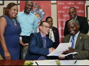 Professor Ishen Kumba Kahwa (seated right), deputy principal, University of the West Indies (UWI), exchanges documents with Mervyn Eyre (seated left), head, Fujitsu, Caribbean, Central America and Mexico, shortly after signing a contract for the acquisition of a supercomputer. Looking on are (from left) Simone Whilby, deputy client executive, Fujitsu; Ainsley Henry, programme manager, UWI; Dr Georgiana Gordon-Strachan, director, Mona Office for Research and Innovation; and Gerard Allenz, climate change senior specialist, IDB, Washington. (Photo: Gleaner)