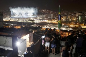 Residents of the Mangueira favela watch the Opening Ceremony from a rooftop. So near, and yet so far away. (Photo: Reuters)