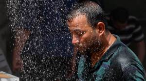 In this July 20, 2016 file photo, an Iraqi man cools off the summer heat by using an open air shower in Baghdad, Iraq. Iraqis are enduring the year's hottest day to date, with temperatures soaring to 51 Celsius degrees (123.8 Fahrenheit) in Baghdad and as much as 53 Celsius (127.4 Fahrenheit) in the southern part of the country. (AP Photo/Karim Kadim, File)