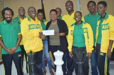 """I think chess is considered a """"sport,"""" although I am not quite sure how, or why. Anyway, it's really good to see Sports Minister Olivia Grange presenting a cheque for US$2 million to  President of the Jamaica Chess Federation, Ian Wilkinson yesterday. The two were joined by members of the team that will represent Jamaica at the 2016 Chess Olympiad in Baku, Azerbaijan from September 1-14. I wish them good luck! (Photo: JIS)"""