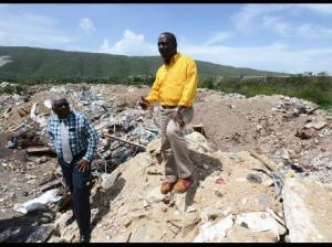 Bedward Gardens in August Town has been transformed into a dump, created by a construction firm working for the University of the West Indies. Charles Simpson, director of compliance and enforement at the National Solid Waste Management Authority (NSWMA), looks on as Audley Gordon, NSWMA chief technical officer, stands atop a section of the illegal dump site. (Photo: Jamaica Star)