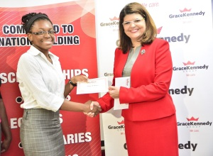 CONGRATS ASHLEY! : Ashley McPherson (left) is all smiles as she receives her Carlton Alexander Bursary Award from Cathrine Kennedy, Group Chief Risk Officer, GraceKennedy. Mcpherson. who is a repeat recipient. was one of 26 children of GraceKennedy employees who were awarded with bursaries valued at $1.5 million at the presentation ceremony on August 30, 2016 at GraceKennedy's head office in Kingston.