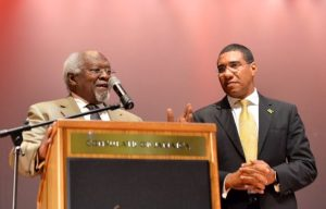 Prime Minister Andrew Holness (right), listens as Dr. Julius Garvey, son of National Hero, the Right Excellent Marcus Mosiah Garvey, addresses a town hall meeting in Queens, New York, USA, on September 22. The Jamaican Government is making a big push for the Obama Administration to grant a pardon to Jamaica's National Hero. (Photo: JIS)
