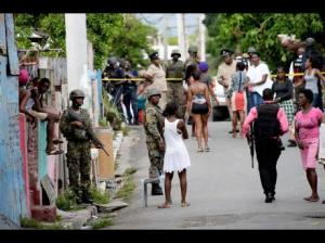 Members of the security forces keep watch as residents converge at the spot where Steve 'Frenchie' Allen was fatally shot by members of a police team last Monday. (Photo: Jermaine Barnaby/Gleaner)