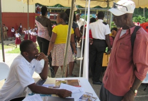 An NIA representative talks with a member of the public at a Health and Information Fair co-sponsored by NIA at Maggotty High School, St. Elizabeth last October. (My photo)